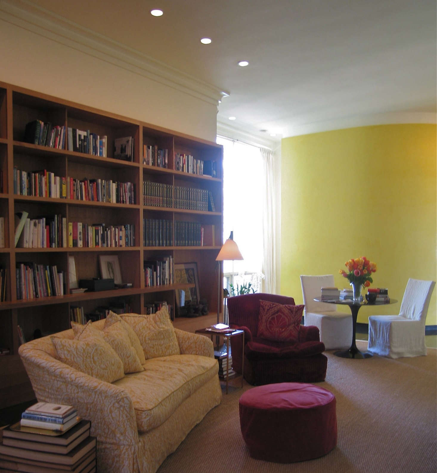 Library, Montecito: This room is actually a very wide hallway, yet the placement of the furnishings and the way architect Michael Paladino placed the curved yellow wall at the end has turned it into a well used room. The traditional seating, made more casual in slipcovers, sits happily with the modern design elements. Photo: Laura Clayton Baker