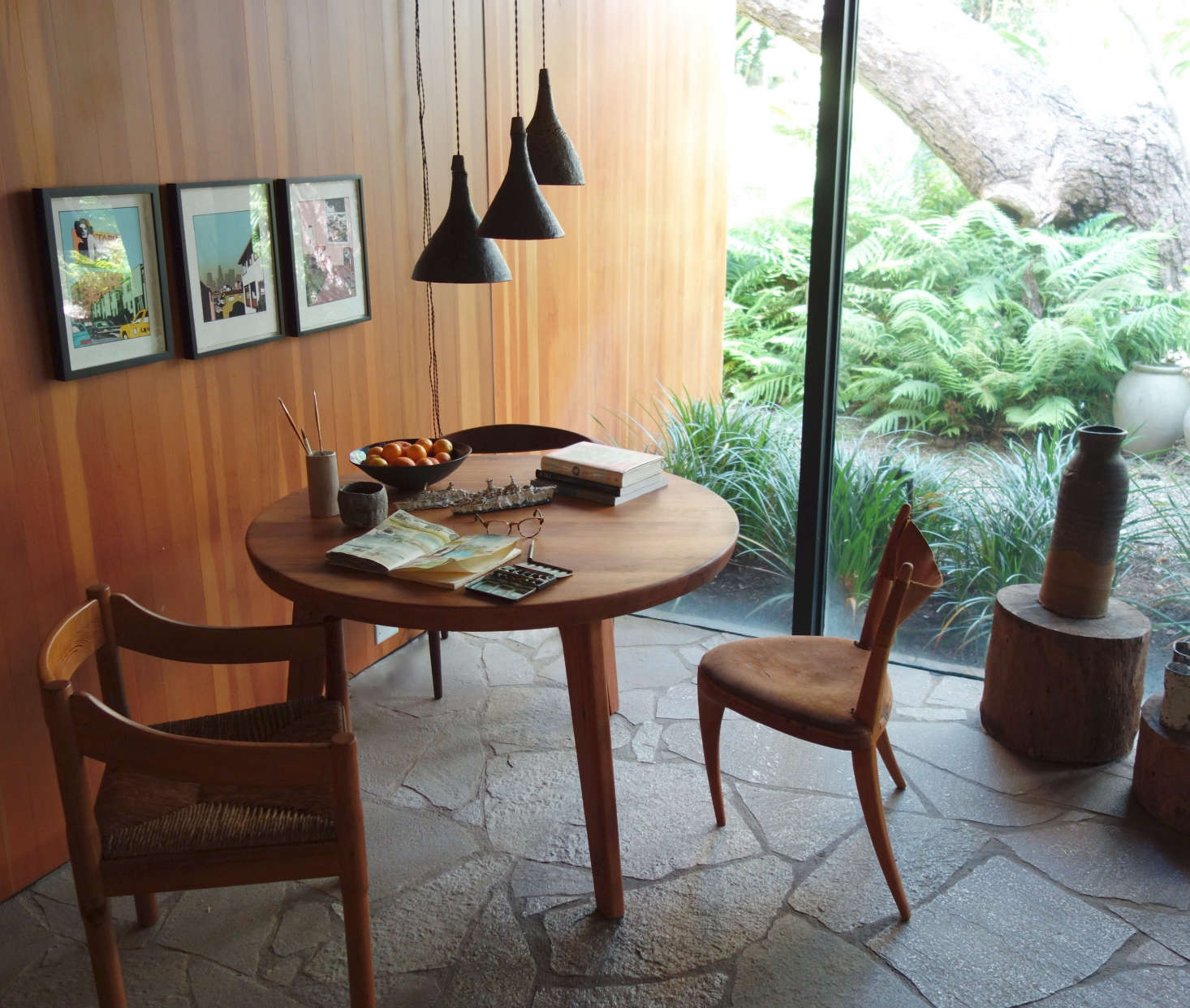 Living Room, Santa Monica: For a corner of theliving room I designed a three legged table inspired by Charlotte Perriand. I selected mismatchedchairs to go around it, and Uplifters Ceramics provided the ceramic pendants overhead. Ken Price drawings are hung on the left, and a 60s vessel sits on a wood tree trunk on the right. Photo: Laura Clayton Baker