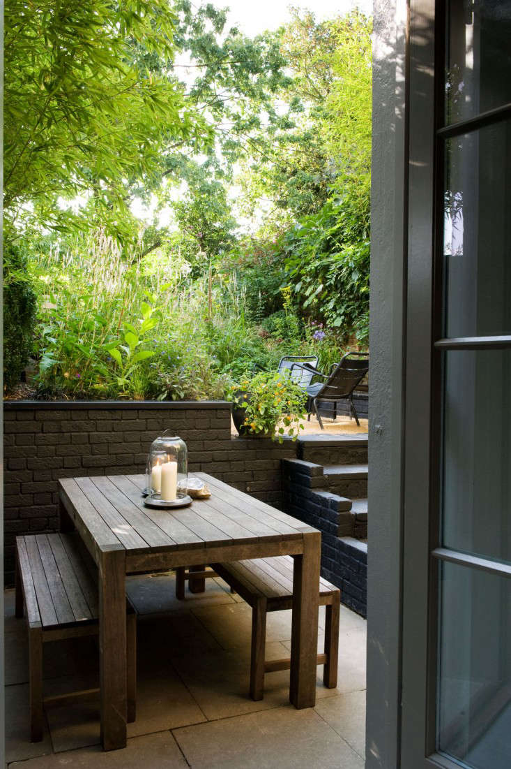 chris-moss-london-garden-dining-table-benches-candles-lanterns-patio-brick-wall-gardenista