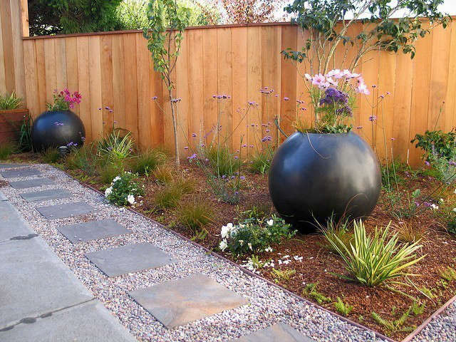 Orb Garden: Orbs create punctuation and angles create 3 different levels in this garden. Bluestone mixed with gravel creates a hopskotch area for the kids and a place for toy trucks while the concrete patio is for adults. Photo: Beth Mullins