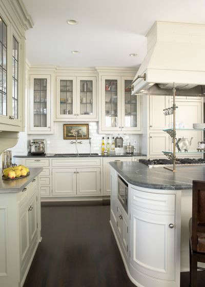 Old World Apartment Traditional Kitchen: Dark stained wood floors, a mix of zinc and marble countertops and leaded glass in the cabinet doors accents a kitchen that functions as the heart of the residence.