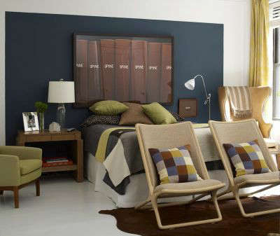 Manhattan Apartment Eclectic Bedroom &#8\2\1\1; Painting a section of wall in a deep ocean blue and hanging a large piece of art over the bed stands in for a traditional headboard.