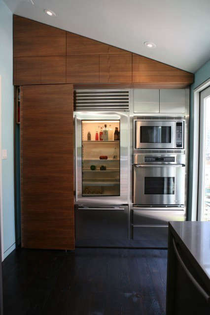 Noe Street Kitchen: A sliding walnut panel (left) hides a stacked washer and dryer, and glides past the Subzero glass front refrigerator. Photo: eurydice galka