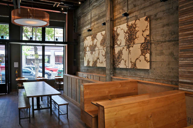Comal&#8\2\17;s Communal table and entry: The architects designed a 48&#8\243; diameter custom copper mesh drum chandelier for one of two communal tables. The artwork is by John Bisbee who heats \1\2&#8\243; steel spikes, forms them into branding irons, and then sears a plywood surface, creating a mandala-like pattern. Repurposed coffee bags cover &#8\2\20;tectum&#8\2\2\1; acoustic panels that form a continuous wainscot around the restaurant.