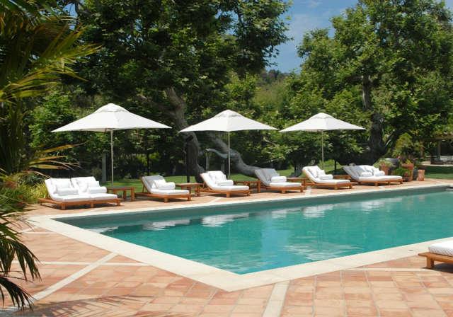 Malibu Estate: Pool viewDesigned to feel like a splendid tropical resort hotel, the tile-lined pool beckons with Italian-designed teak lounge chairs. Photo: Russ Cletta