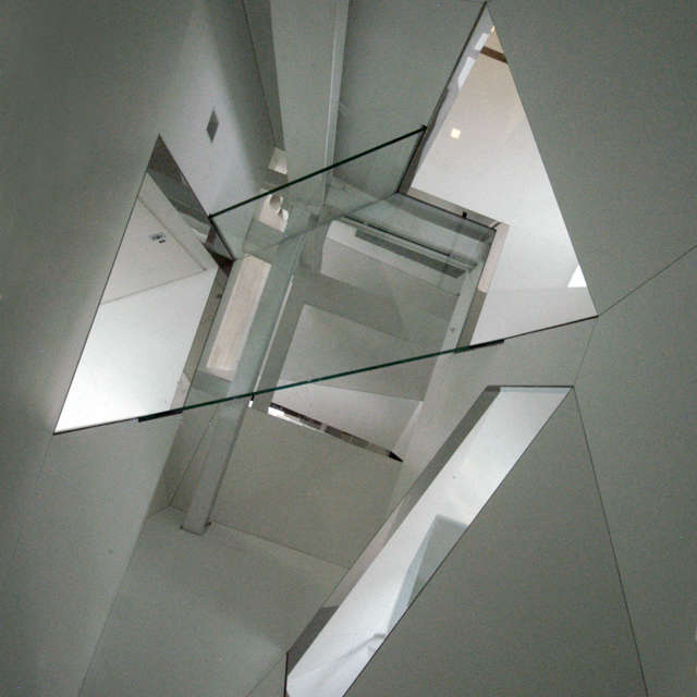 Stairwell_viewed from Attic: The glass floor at Attic level offers a view down through the four-story facetted stairwell,spanned at the third level by a structural glass bridge.