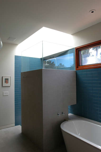 Winebaum Shower and Bath &#8\2\1\1; A blue tiled bathroom with natural light from the skylight over the shower. Clerestory windows permit more natural light and provide a well lit bathroom.