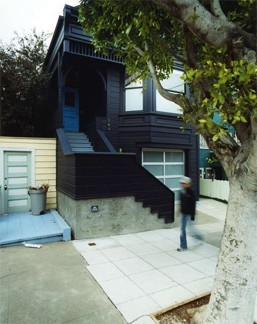 Clipper Street Residence SFCA: Clipper Street Residence: The gingerbread of the existing Victorian house is collected under a blue-black monochrome. Space Invader makes his mark on the architectural concrete base for the tongue of the new stair. The cyan painted door calls out entry to the residence above, a new service station door to the garage and studio below. Photo: Todd Hido