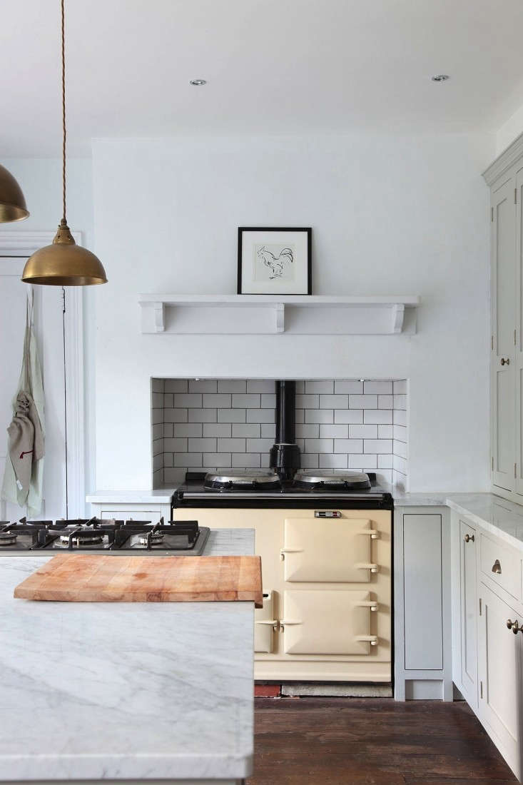 A Minimalist English Kitchen is outfitted with a traditional Aga range (and an extra cooktop, located on the island).