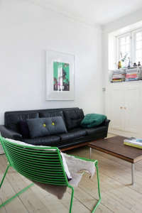 Anne Mette Skodbor, Copenhagen home, green chair and black leather sofa in living room | Remodelista