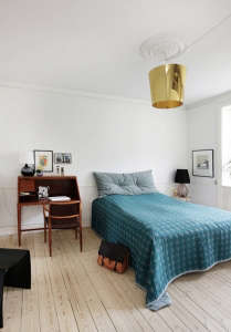 Anne Mette Skodbor, Copenhagen home, blue bedspread and gold upside down pendant lamp | Remodelista