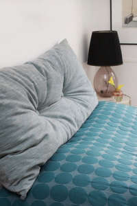 Anne Mette Skodbor, Copenhagen home, gray cushion on teal blue bedspread | Remodelista
