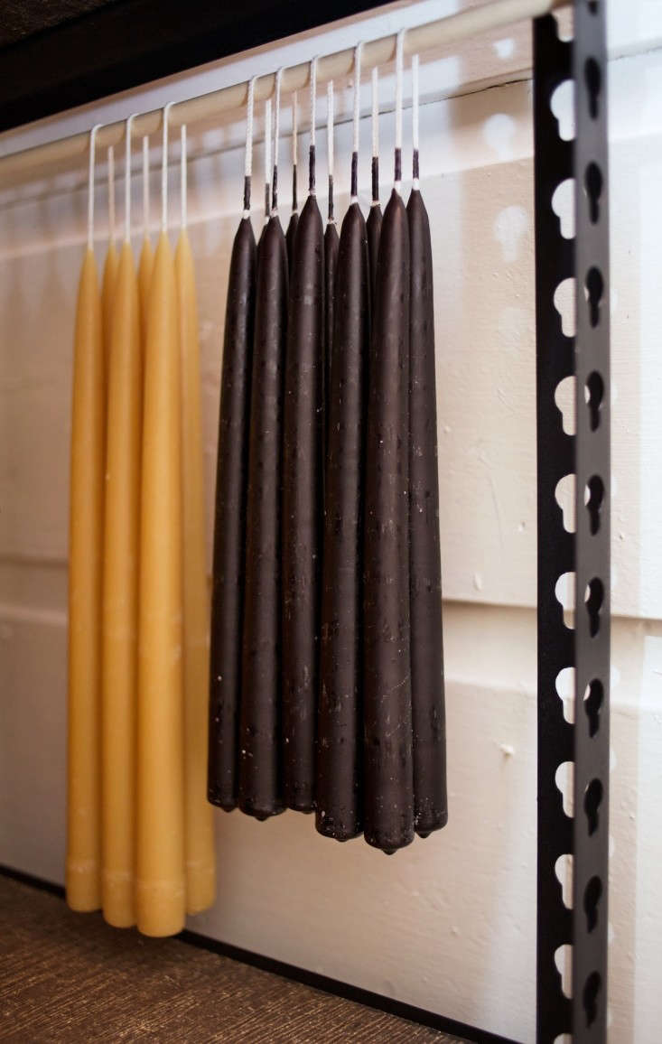 Beeswax Taper Candles and Black Taper Candles Hanging in Storage Space, Remodelista