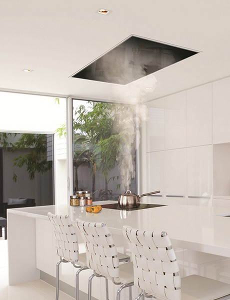A recessed hooddraws steam in a Corian model kitchen in the UK.