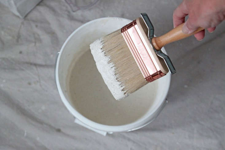 DIY limewash putting paint on brush, by Justine Hand for Remodelista_edited-1