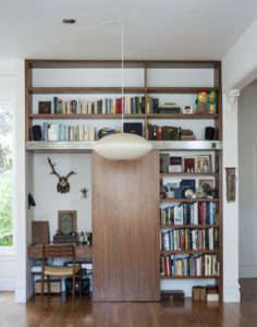 Dagmar Daley and Zak Conway sliding bookshelf home office | Remodelista