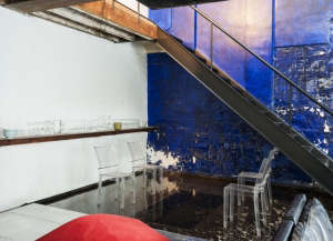 David Ling Architect, Live/Work sudio in New York, cobalt blue wall, welded blackened metal stairs, Kartell Louis Ghost chairs by Philippe Starck | Remodelista