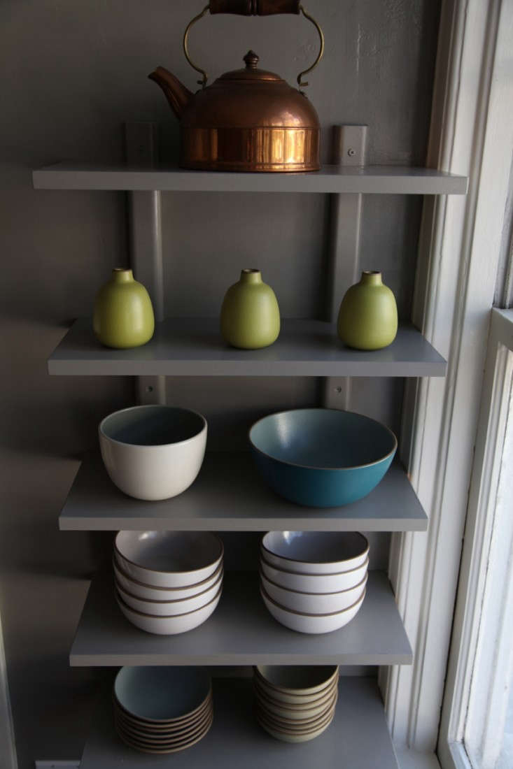 Heath Ceramics Bowls and Vases and Copper Tea Kettle on Gray Painted Shelving in Apartment Kitchen, Remodelista