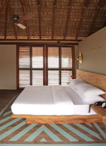 Bedroom of Hotel Escondido in Mexico with Thatched Palm Roof and Painted Blue Striped Floor, Remodelista