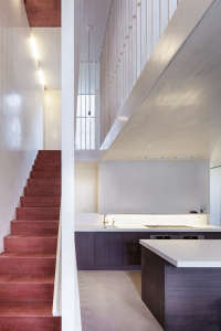 Jonathan Tuckey, Submariner's House, red pigmented cement stair down to kitchen, London | Remodelista