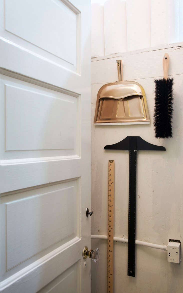 Meredith-Swinehart-Brush- Dustpan-T-square-Yard-Stick-on-utility-closet-wall- Remodelista
