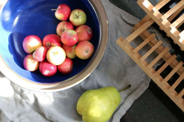 Mini apples in Heath Ceramics bowl with pear on linen towel, Remodelista