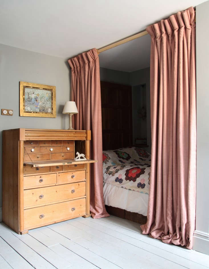 Shut out the light (and create a sleep cocoon) with a curtained bed. Photograph from Out with the New: Reinventing the Past in a London Remodel.