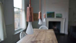 Plumen 002, Designer Low Energy Bulb, Line of Copper Capped Bulbs in Dining Room | Remodelista
