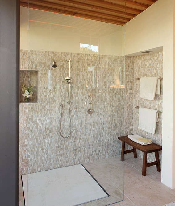 Schicketanz Bathroom with White and Tan Tile Walls and Clear Glass Shower and Wood Bench, Remodelista