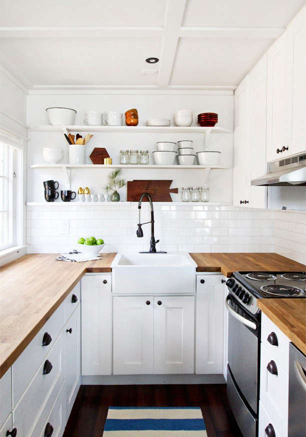 """A butler's sink and overhead open shelves provide the focus in designer and blogger Sarah Sherman Samuel's small cabin kitchen on the shores of Lake Michigan. (Have a look at Samuel's newly remodeledkitchen in LA employing what she calls """"the ultimate Ikea hack"""": Ikea cabinets and custom doors). Photograph via Smitten Studio."""
