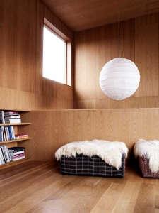 Villa Weinberg, Aarhus, Denmark, wood lined den, concrete floors, sheepskin throws on benches, Noguchi Akari Pendant | Remodelista