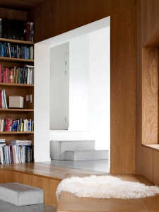 Villa Weinberg, Aarhus, Denmark, concrete sleepers as steps, wood lined den, concrete floors, sheepskin throw on bench | Remodelista
