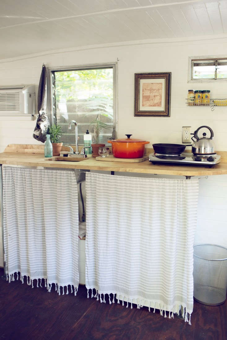 Turkish towels repurposed as curtains hide kitchen essentials in this vintage camper. SeeThe Ultimate Backyard Guest Retreat, Sixties Camper Edition. Photograph byLaura Dartfor J. Wes Yoder.