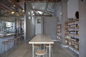 Handsome Coffee Roasters with coopper pipe shelving and mapel stools and table
