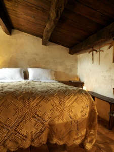 Bed in medieval hotel in Italy with yellow crochet bedspread