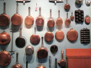 Copper pots hanging on a pegboard in Julia Childs' kitchen