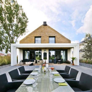 Arjen-Reas-Zoetermeer-thatched-roof-walls-lime-walls-wood-deck-outdoor-table-chairs