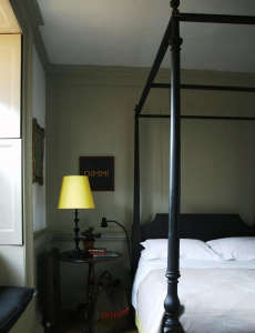 Marianna-Kennedy-Spitalfields-house-master-bedroom-yellow-lampshade-black-painted-bedframe-hand-painted-sign