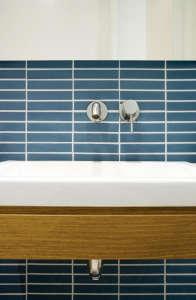 Uniform-Design-Minimalist-bathroom-style-blue-horizontal-tiles-white sink-wood-fascia