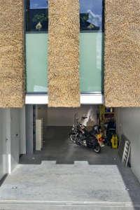 Arjen-Reas-Zoetermeer-thatched-roof-walls-lime-walls-glazed-openings-motorcycle
