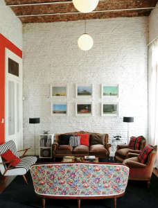 Buenos Aires apartment, red and white color scheme, white-washed brick walls with red stripe, floral fabric covered sofa, Remodelista