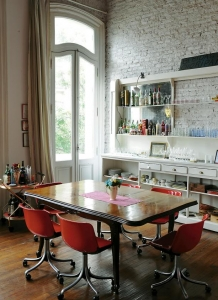 Buenos Aires apartment, red and white color scheme, white-washed brick walls, midcentury red office chairs, Remodelista