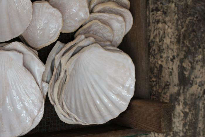Ceramics are molded from beach shells, then coated in a high-gloss white glaze.