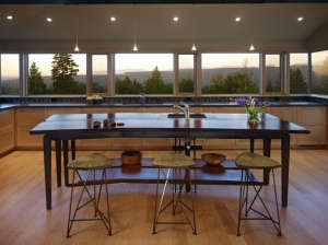 Overall-kitchen-view,showing-island-table,-counter, Remodelista: Best Kitchen Space, The bath has fir paneling and glass walls toward the garden.  The overall feeling is that of bathing in nature.  Suspended steel mirror frames hang down at the vanity.  F