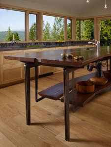 island-table-made-from-reclaimed-elm,-limestone,-s, Remodelista: Best Kitchen Space, The bath has fir paneling and glass walls toward the garden.  The overall feeling is that of bathing in nature.  Suspended steel mirror frames hang down at the vanity.  F