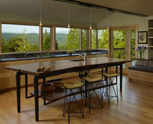 general-view-of-island-table,-work-counter,-and-se, Remodelista: Best Kitchen Space, The bath has fir paneling and glass walls toward the garden.  The overall feeling is that of bathing in nature.  Suspended steel mirror frames hang down at the vanity.  F