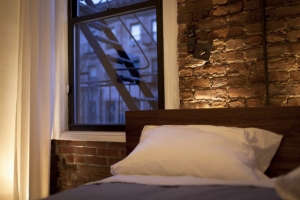 The-exposed-brick-wall-overlooking-the-street-is-u, Remodelista: Best Bedroom Space, The decor and furnishings of the guest room are all pertinent to the site's location in the East Village. The Sanborn map is of the neighborhood and includes the building