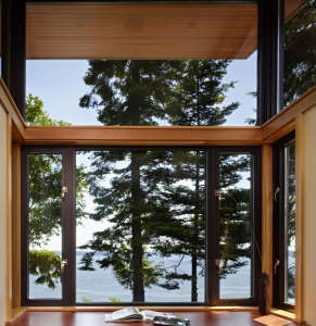 detail-of-desk-integrated-with-wraparound-windows, Remodelista: Best Office Space, This small, compact office is really a glazed alcove, with the desk surface integrated seamlessly with wraparound windows and a sweeping view of the Hood Canal, a long, fjo