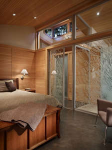 master-bedroom-with-clear-fir-paneling,-glass-wall, Remodelista: Best Bedroom Space, The bedroom has fir paneling and glass walls toward the garden. The interior wall between the bedroom and bath is also a glass wall, with a hand-drawn etched glass patter