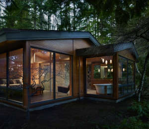 exterior-view-of-master-bedroom-and-master-bath, Remodelista: Best Bedroom Space, The bedroom has fir paneling and glass walls toward the garden. The interior wall between the bedroom and bath is also a glass wall, with a hand-drawn etched glass pattern f